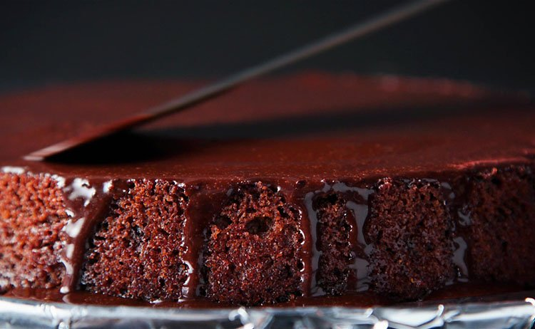 spreading the vegan icing with an offset spatula on the sides and top of the eggless chocolate cake.