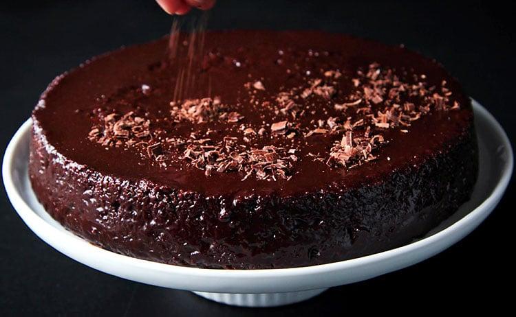 vegan chocolate cake being decorated with chocolate shavings