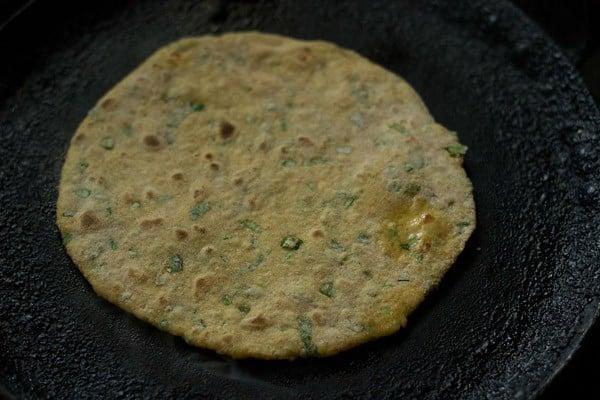 cooking mix veg paratha on a tawa