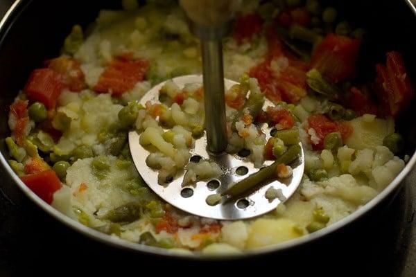 mashing vegetables to make mix veg paratha recipe