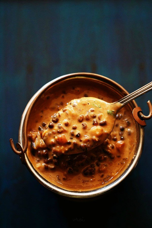 dal makhani served in a small and taken in a spoon on a dark blue board