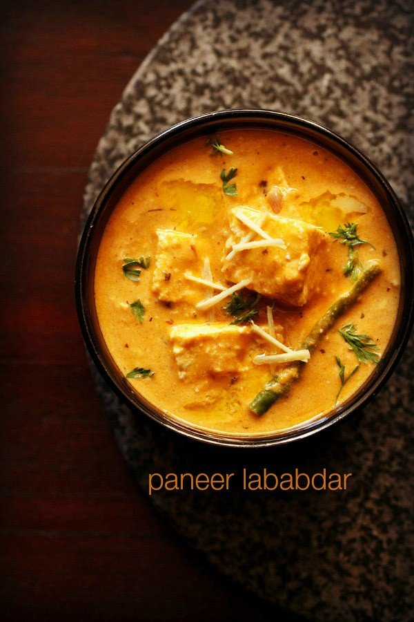 paneer lababdar in a black bowl with ginger julienne on top