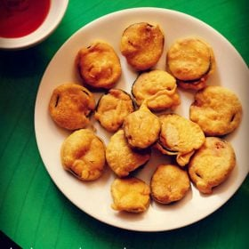 brinjal pakora or brinjal bajji on a white plate with a side of chutney at the side