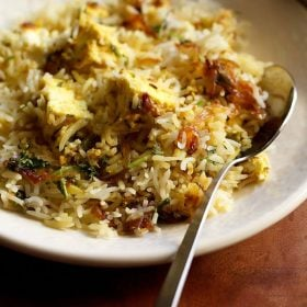 paneer biryani served in a cream shallow plate with a steel spoon by the side on a brown wooden board