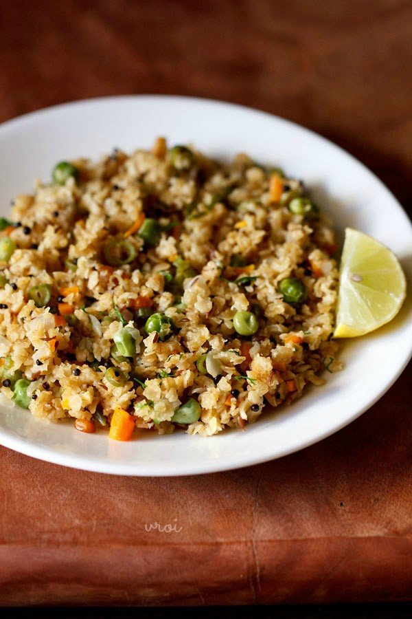 oats upma with lemon wedge on white plate on a brown board