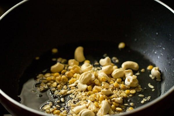 cashews, lentils being fried in oil in black pan