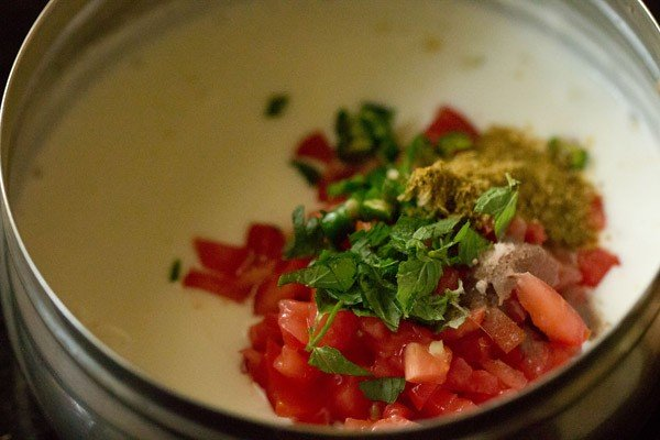 adding tomatoes and spices for raita