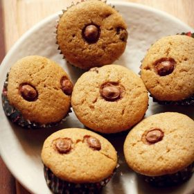healthy chocolate chip muffins arranged neatly on a round plate placed on a bamboo board