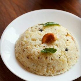 pongal recipe garnished with a cashew and curry leaves and served in a white plate with a white bowl of mango pickle by side