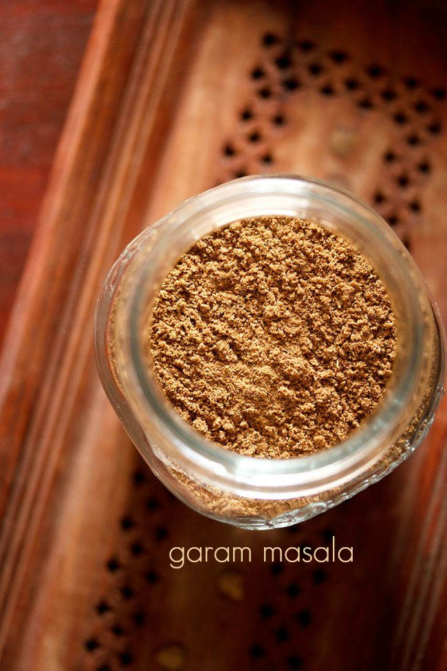 garam masala powder in a glass  jar on a brown wooden tray