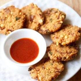 dal vada arranged neatly on a white plate next to a small white bowl of red chutney