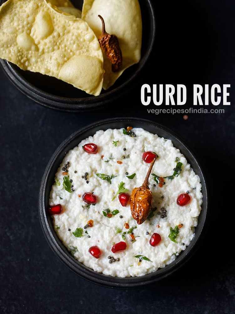 curd rice served in a wooden bowl on a dark grey black board. curd rice is garnished with chopped coriander leaves, some pomegranate arils and fried sun dried chilly. fried papaddum served as as side.