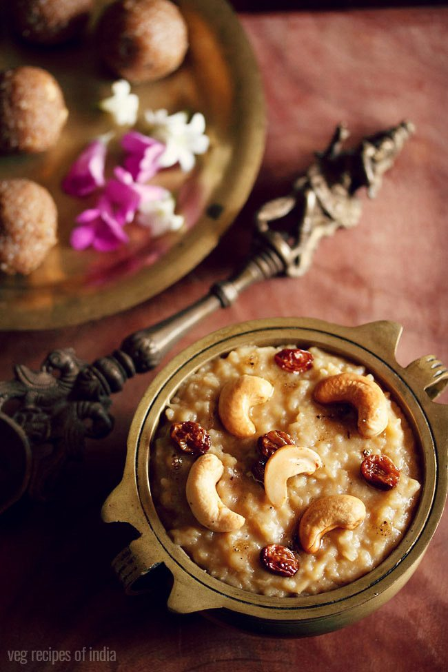 sakkarai pongal served in an antique brass pan with a side of an antique brass spoon and some ladoo and dark pink and white flowers on a brass plate