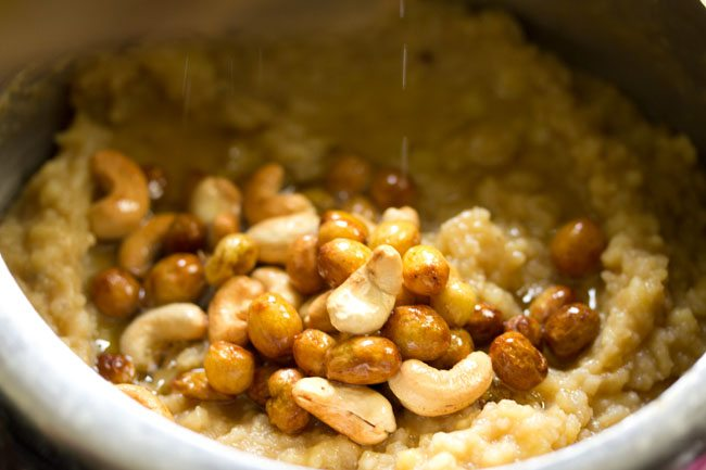 fried mixture of raisins, cashews and ghee on the mashed rice and lentils mixture