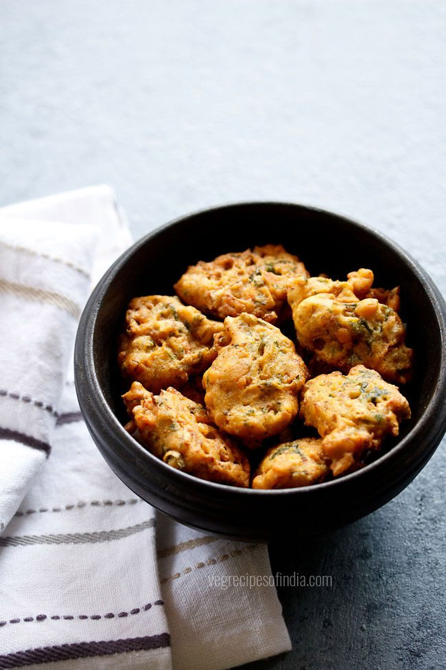 mix vegetable pakora in a black wooden bowl placed next to a white striped kitchen linen