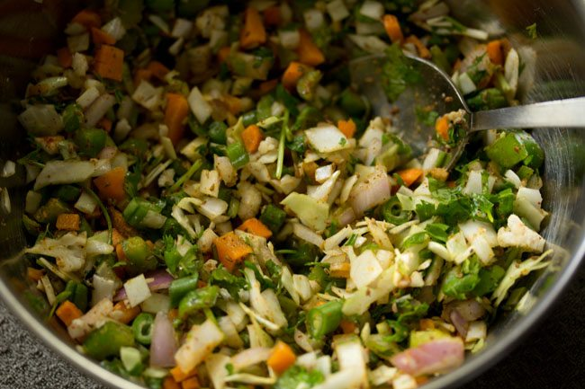 veg pakora ingredients mixed with a spoon