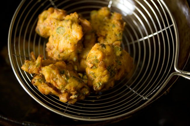crisp, golden fried mixed vegetable pakora in a steel spider-spoon