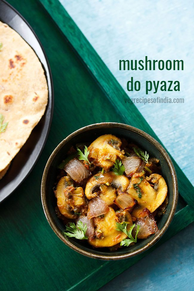 mushroom do pyaza garnished with cilantro sprigs in a dark olive green ceramic bowl on a dark green board with a side of roti with text layovers