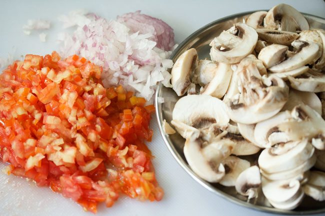 finely chopped onions, tomatoes and chopped mushrooms on a white cutting board