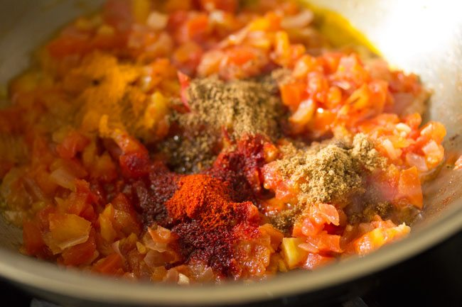 ground spices added to tomatoes for making potato curry