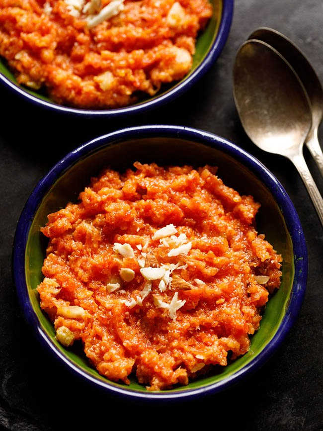 instant pot gajar halwa served in a two dark green small plates with two brass spoons at the sides