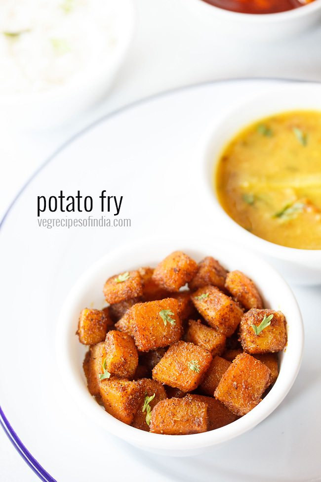 potato fry served in a bowl placed on a white plate with lentil curry in another bowl