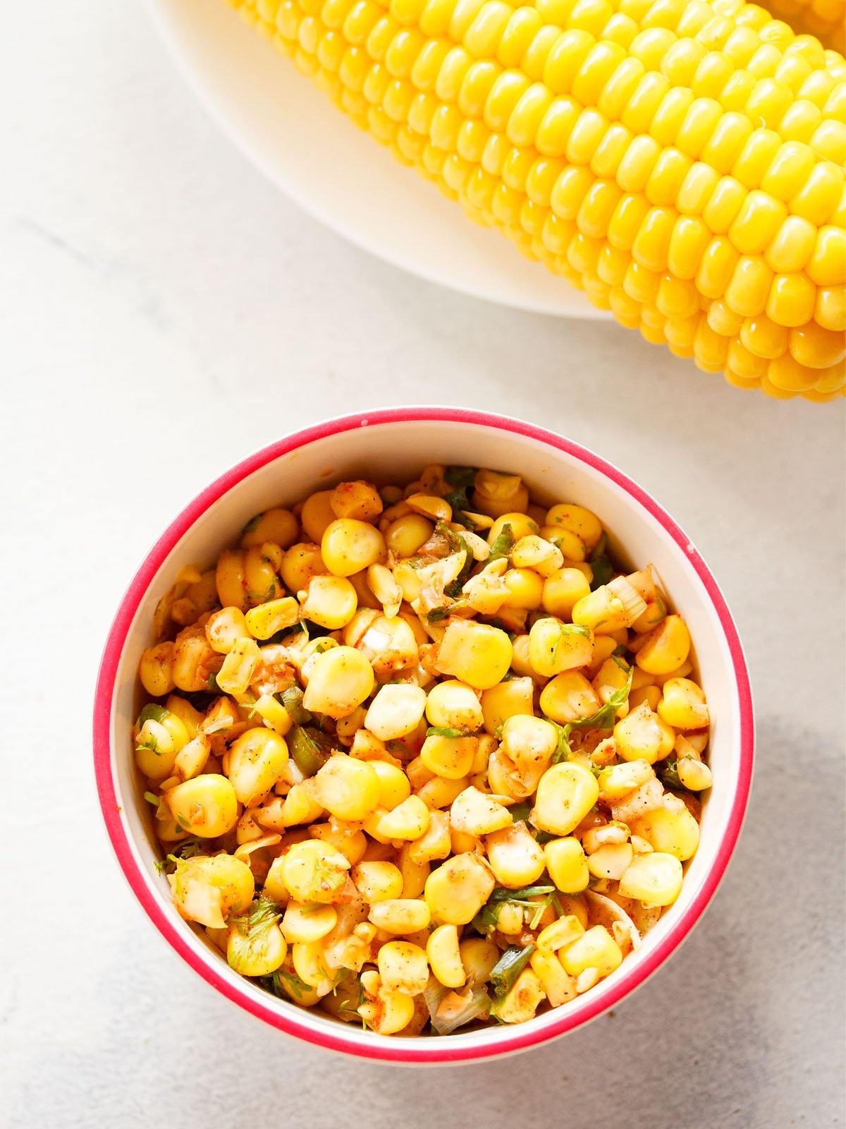 sweet corn salsa served in a dark pink rimmed white bowl on a white background