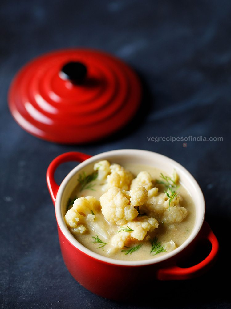 top shot of cauliflower with fresh herbs in liquid broth, served in small red bowl