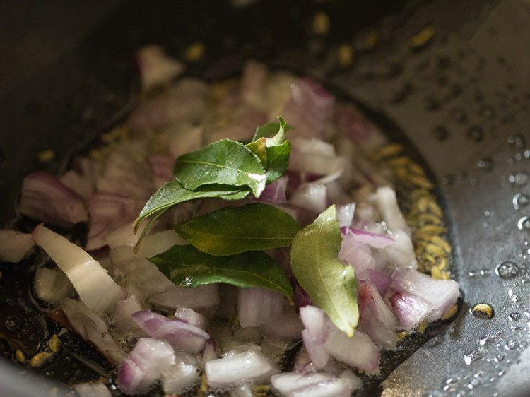 close up shot of onions and curry leaves cooking in saucepan