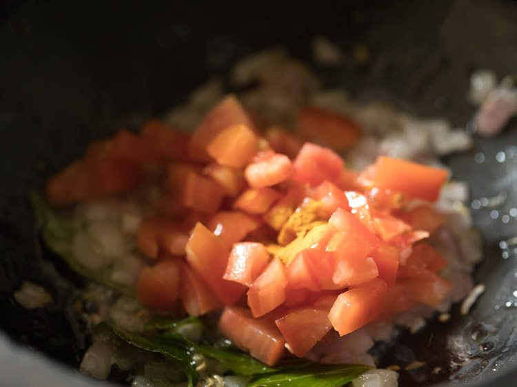 close up shot of chopped tomatoes cooking in saucepan