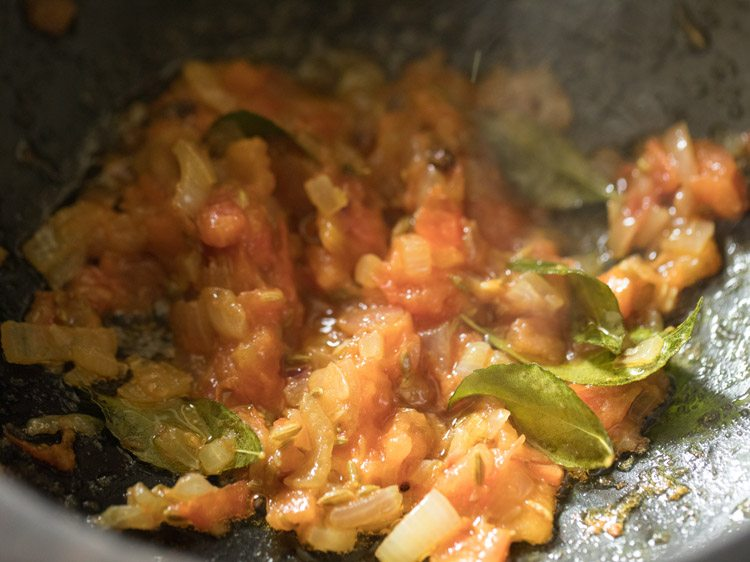 close up shot of onion and tomatoes mixture crushed up and mixed in saucepan