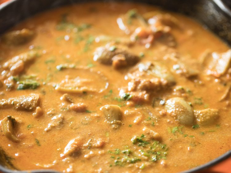 Closeup shot of baingan masala cooking in skillet.