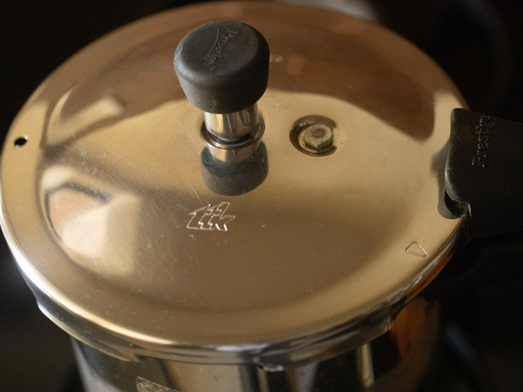 covering pressure cooker tightly with lid and pressure cooking chana