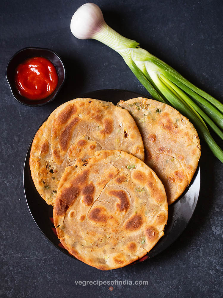green onion pancakes places on a black ceramic plate on a black board with sriracha sauce served in a small black bowl on left side and a stalk of spring onion placed on the right side of the plate.