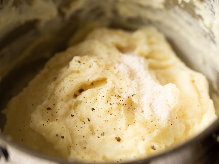 salt and black pepper sprinkled on mashed potatoes in the pan
