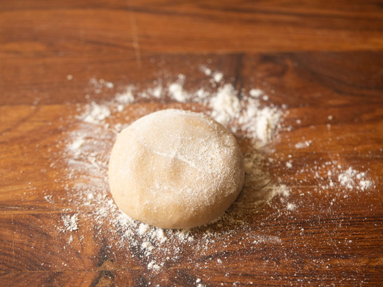 each sliced dough part rolled into a ball and then slightly flattened on rolling board with flour sprinkled