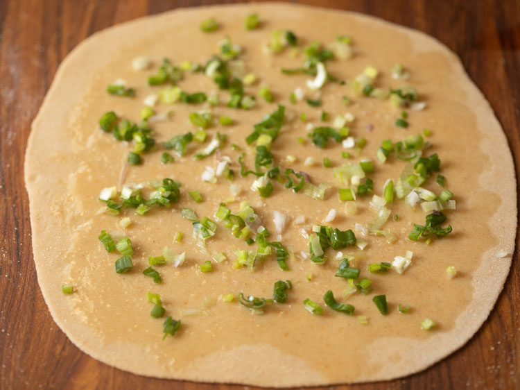 scallions sprinkled on the rolled dough