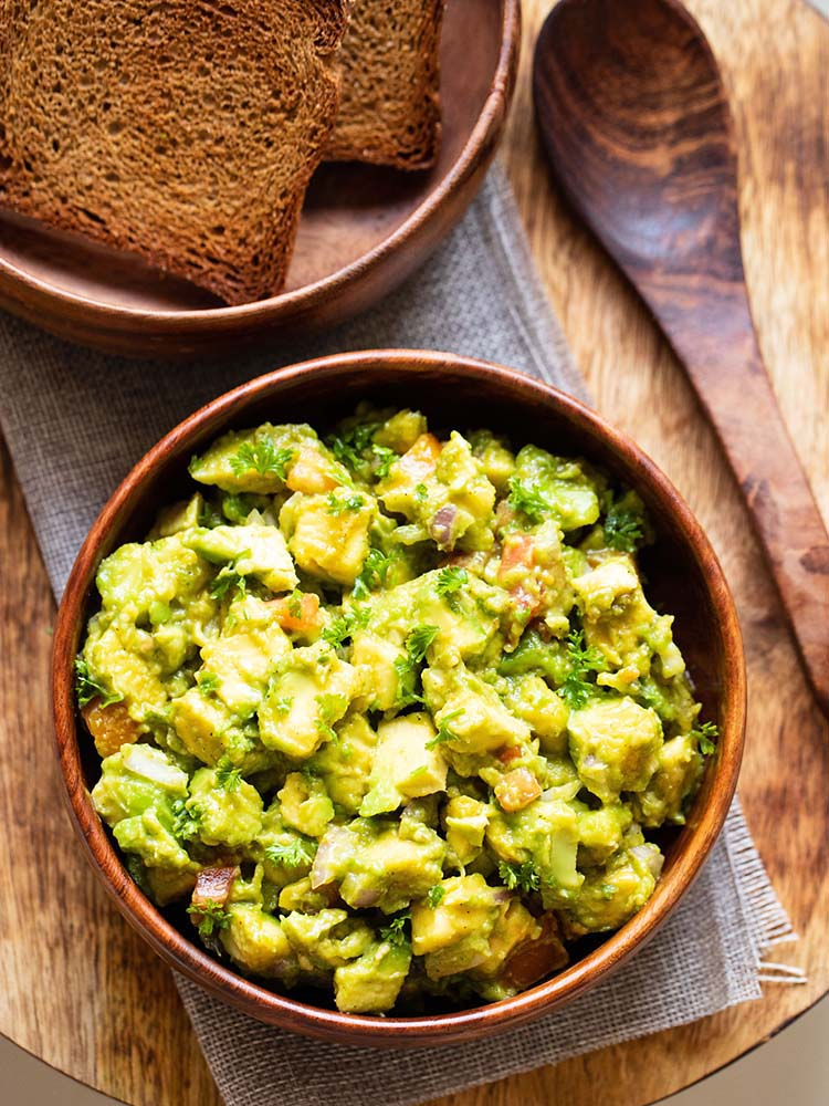 avocado salad served in a wooden bowl with a wooden spoon and some toasted bread in the background