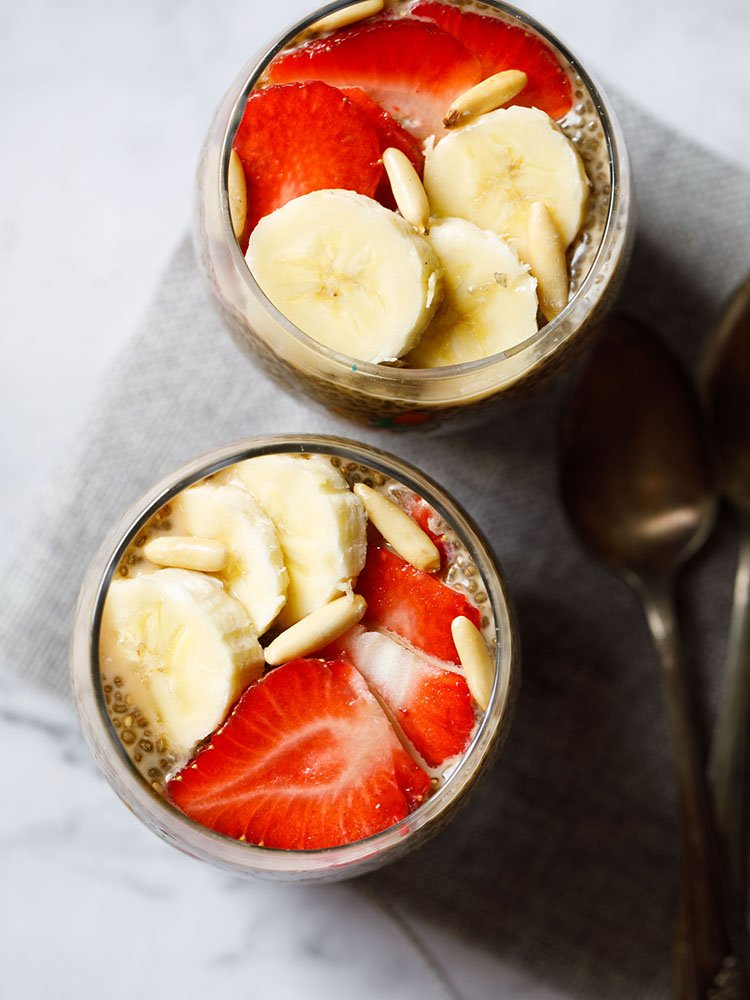 topped with sliced bananas, strawberries, pine nuts the two glasses of chia seed pudding are placed on a gray jute mat on a white marbled board