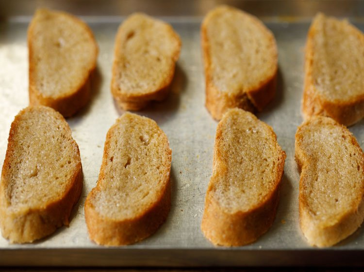 baguette slices brushed with olive oil and placed on baking tray