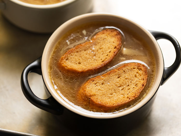 toasted baguette slices being placed on the soup.