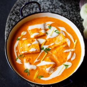 paneer butter masala served in a blue rimmed white pan, garnished with cream and cilantro