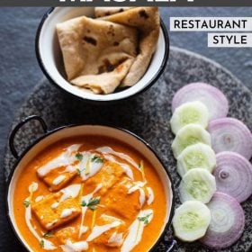 paneer butter masala served in a blue rimmed white pan, garnished with cream and cilantro with a side of roti, sliced cucumber and onions.