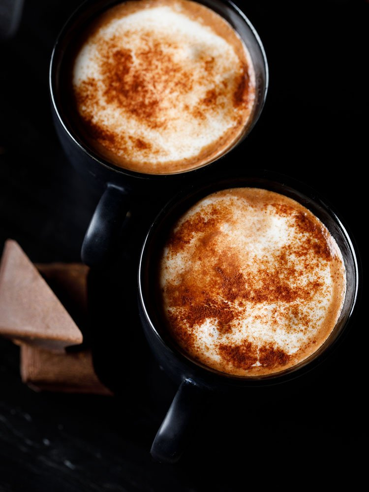 hot chocolate sprinkled with cocoa powder and served in 2 black cups on a black marble board