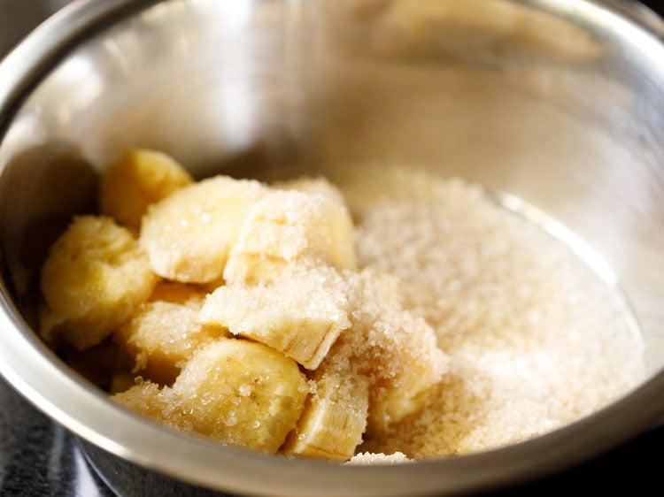 chopped bananas and sugar in mixing bowl