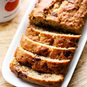 Chocolate Chip Banana Bread Loaf sliced on a white platter placed on a wooden board.