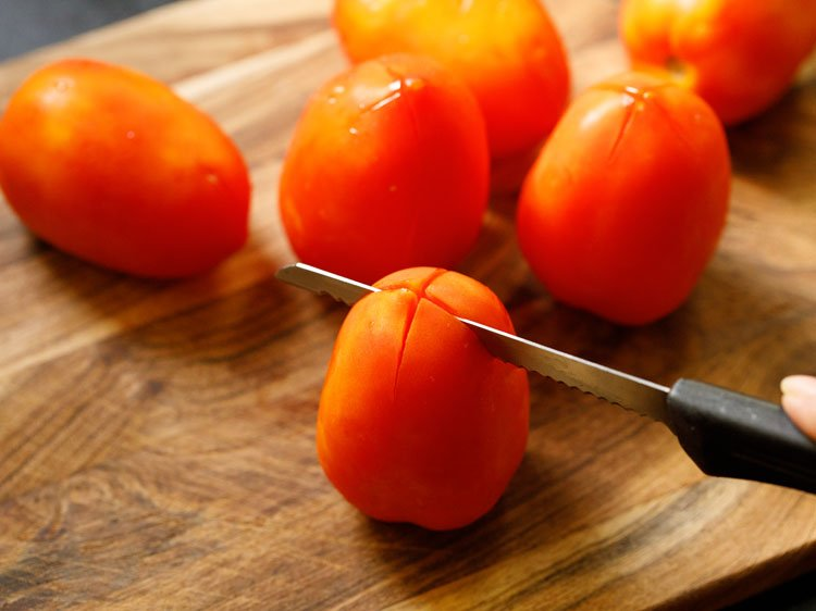 giving criss cross slits on the base of the tomatoes