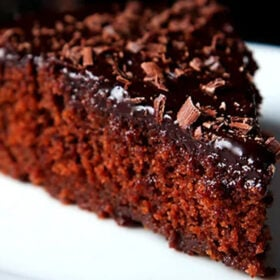 closeup shot of a triangular wedge of eggless chocolate cake on a white plate