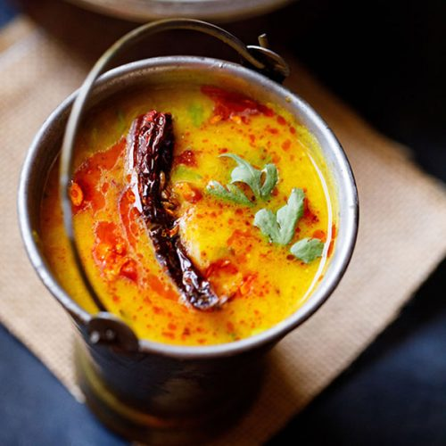 dal tadka garnished with cilantro and a topped with fried red chilli with some fried cumin and some red colored oil in a small brass bucket on a light brown jute mat