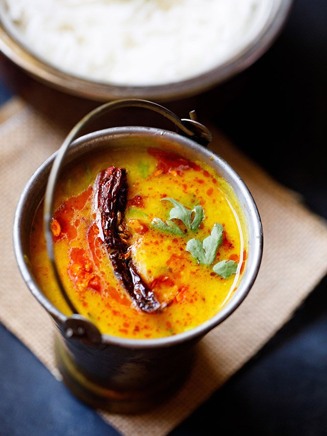 dal tadka garnished with cilantro and a topped with fried red chilli with some fried cumin and some red colored oil in a small brass bucket on a light brown jute mat with a bowl of steamed rice kept above on the top-right.